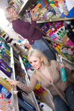 Женщины в хороших настроениях выбирая тензиды в магазине Стоковая Фотография RF