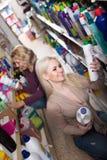 Женщины в хороших настроениях выбирая тензиды в магазине Стоковое Изображение