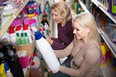 Женщины в хороших настроениях выбирая тензиды в магазине Стоковые Изображения RF