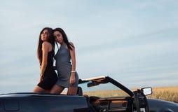 2 женщины в черном автомобиле на дорогах обочины Стоковое Изображение RF