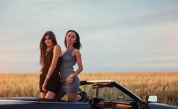 2 женщины в черном автомобиле на дорогах обочины Стоковое Изображение