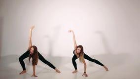 2 женщины в черном спорте носят делать тренировку йоги видеоматериал