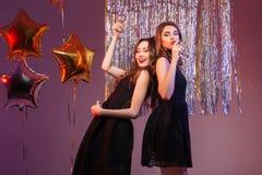 2 женщины в шампанском черного платья выпивая Стоковые Фото