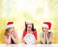 Женщины в шляпах хелпера santa при часы показывая 12 Стоковое Изображение RF