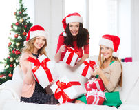 Женщины в шляпах хелпера santa с много подарочных коробок Стоковые Фото