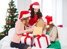 Женщины в шляпах хелпера santa с много подарочных коробок Стоковое Фото