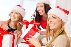 Женщины в шляпах хелпера santa с много подарочных коробок Стоковое Изображение