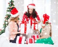 Женщины в шляпах хелпера santa с много подарочных коробок Стоковые Изображения RF