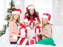 Женщины в шляпах хелпера santa с много подарочных коробок Стоковое фото RF