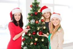 Женщины в шляпах хелпера santa украшая дерево Стоковые Фотографии RF