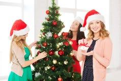 Женщины в шляпах хелпера santa украшая дерево Стоковое фото RF