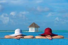 2 женщины в шляпе сидя на краю бассейна Стоковые Изображения RF