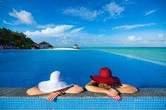 2 женщины в шляпе сидя на краю бассейна Стоковое фото RF