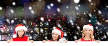 Женщины в шляпе хелпера santa с пустой белой доской Стоковая Фотография
