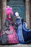 2 женщины в ярко покрашенных костюмах стоя перед старой голубой дверью в Венеции во время масленицы Стоковое фото RF