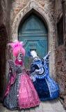 2 женщины в ярко покрашенных масках и голубых и розовых костюмах стоя перед старой голубой дверью в Венеции во время масленицы Стоковые Изображения RF
