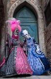 2 женщины в ярко покрашенных масках и костюмы стоя перед старой голубой дверью в Венеции во время масленицы Стоковое Изображение RF