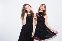 2 женщины в blak одевают держать стеклянный с шампанским Стоковые Фотографии RF
