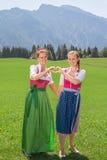 2 женщины в dirndl формируя сердце с ее руками Стоковая Фотография