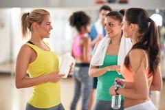 Женщины говоря и освежая на проломе в классе фитнеса стоковое фото rf