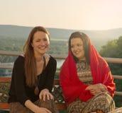 2 женщины говоря на балконе в заходе солнца Стоковая Фотография