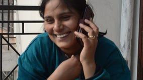 Женщины говоря на смартфоне с его другом акции видеоматериалы