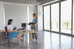 Женщины говоря на столе в пустом офисе Стоковое Фото