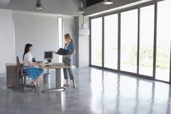Женщины говоря на столе в пустом офисе Стоковое Изображение RF