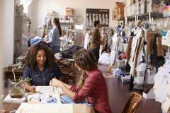 2 женщины говоря на таблице в одежды конструируют студию Стоковое фото RF