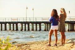 2 женщины говоря отдыхать на пляже Стоковое фото RF
