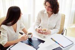 2 женщины говоря о что-то и кофе питья в офисе Стоковые Изображения RF