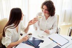 2 женщины говоря о что-то и кофе питья на работе Стоковая Фотография