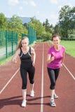 2 женщины готовой для того чтобы участвовать в гонке на идущем следе Стоковые Изображения RF