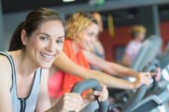 Женщины группы ехать на велотренажере в спортзале стоковая фотография