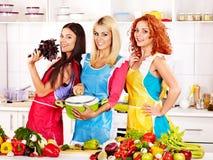 Женщины группы подготавливая еду на кухне. Стоковое Изображение