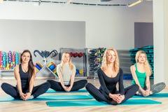 женщины делают йогу, выполняют протягивать тренировки Стоковые Изображения RF