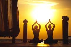2 женщины делают йогу на восходе солнца около моря Стоковые Фотографии RF