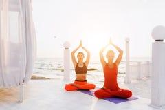 2 женщины делают йогу на восходе солнца около моря Стоковые Фото