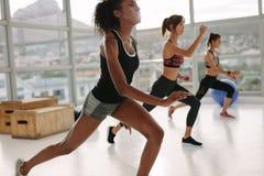 Женщины делая интенсивную разминку в спортзале Стоковые Изображения