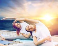 Женщины делая йогу работают outdoors Стоковые Фотографии RF