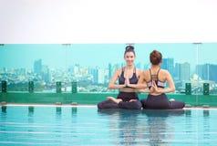 Женщины делая представление йоги на бассейне Стоковое фото RF