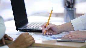 2 женщины делая примечания и обсуждая проект, эффективную сыгранность на офисе Стоковое Изображение