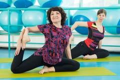Женщины делая тренировку йоги в спортзале Стоковое Изображение