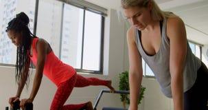 Женщины делая тренировку с машиной rowing 4k видеоматериал