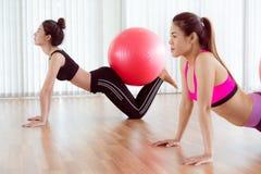 Женщины делая тренировку с шариком пригонки в классе спортзала Стоковые Фото