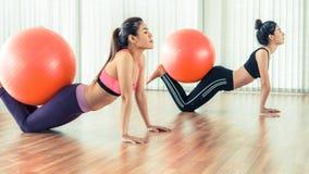 Женщины делая тренировку с шариком пригонки в классе спортзала Стоковые Изображения