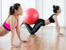 Женщины делая тренировку с шариком пригонки в классе спортзала Стоковые Изображения RF