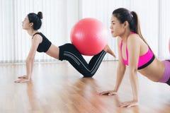 Женщины делая тренировку с шариком пригонки в классе спортзала Стоковые Фотографии RF