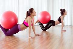 Женщины делая тренировку с шариком пригонки в классе спортзала Стоковое фото RF
