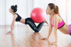 Женщины делая тренировку с шариком пригонки в классе спортзала Стоковая Фотография